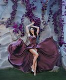 Λεπτή ελκυστική κυρία όπως την εικόνα του πανέμορφου καλλιτέχνη, πετώντας κυματίζοντας πορφυρό μακρύ φόρεμα σατέν όπως τα κτυπήμα στοκ εικόνες με δικαίωμα ελεύθερης χρήσης