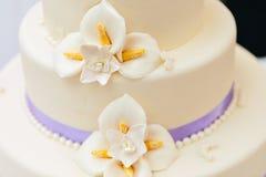 Λουλούδια αμυγδαλωτού και πορφυρή κορδέλλα στο γαμήλιο κέικ στοκ εικόνα