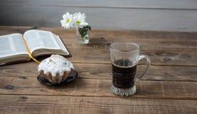 Λουλούδια ενός καφέ cupcake και ανοικτό βιβλίο σε ένα ξύλινο υπόβαθρο στοκ φωτογραφία