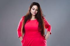 Λυπημένος συν το πρότυπο μόδας μεγέθους στο κόκκινο φόρεμα, παχιά γυναίκα στο γκρίζο υπόβαθρο στοκ φωτογραφία με δικαίωμα ελεύθερης χρήσης