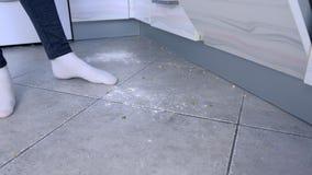 Μάγειρες γυναικών που στέκονται στο βρώμικο πάτωμα στην κουζίνα Περισσεύματα και crumbs στο πάτωμα κουζινών Πόδια στις άσπρες κάλ απόθεμα βίντεο