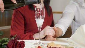 Μέσος πυροβολισμός των νέων χεριών ζευγών στον πίνακα Σε αργή κίνηση του σερβιτόρου που χύνει CHAMPAGNE στην αγάπη του ζεύγους πο φιλμ μικρού μήκους