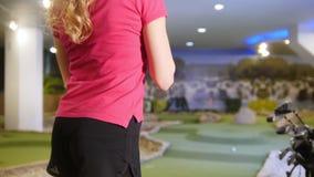 μίνι παιχνίδι γκολφ Μια νέα γυναίκα που παίζει το μίνι γκολφ στο εσωτερικό Χτύπημα της σφαίρας και τοποθέτηση του ραβδιού στον ώμ απόθεμα βίντεο