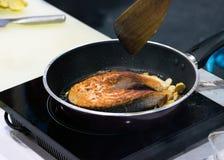 Μαγειρεύοντας μπριζόλα σολομών, τηγανητά σολομών στο τηγάνι στοκ εικόνες
