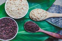 Μαγειρευμένα πορφυρά μούρο ρυζιού και καφετί ρύζι στο κύπελλο πέρα από το πράσινο υπόβαθρο φύλλων στοκ φωτογραφία