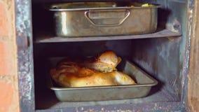 Μαγειρευμένο κοτόπουλο με τη χρυσή κρούστα που μαγειρεύεται σε έναν αγροτικό φούρνο απόθεμα βίντεο