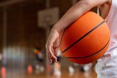 Μαθητής με την καλαθοσφαίριση που στέκεται στο γήπεδο μπάσκετ στοκ εικόνες
