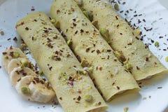 Μαλακός στενός επάνω εστίασης 3 crepes οι τηγανίτες με τις μπανάνες που ολοκληρώνονται με τα ξέσματα σοκολάτας και cocos και τα φ στοκ φωτογραφία