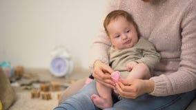 Μαμά που βάζει τις ρόδινες κάλτσες στο λατρευτό κοριτσάκι, το νεογέννητους ιματισμό και τα εξαρτήματα απόθεμα βίντεο