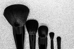 Μαύρες βούρτσες makeup στη λαμπρή ασημένια επιφάνεια υποβάθρου στοκ εικόνες