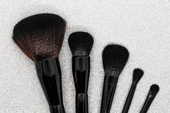 Μαύρες και καφετιές βούρτσες makeup στη λαμπρή ασημένια επιφάνεια υποβάθρου στοκ εικόνες