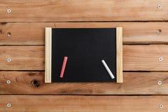 Μαύρος πίνακας στο ξύλινο πλαίσιο στο ξύλινο υπόβαθρο με την κιμωλία στοκ φωτογραφία με δικαίωμα ελεύθερης χρήσης