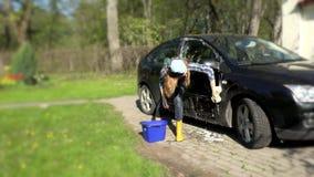 Μαύρο αυτοκίνητο πλυσίματος κοριτσιών με το σαπωνώδες σφουγγάρι φιλμ μικρού μήκους