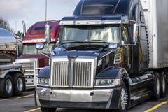Μαύρο μεγάλο σύγχρονο ημι φορτηγό εγκαταστάσεων γεώτρησης με το ημι ρυμουλκό που στέκεται στη στάση φορτηγών με άλλη τα ημι φορτη στοκ εικόνα με δικαίωμα ελεύθερης χρήσης