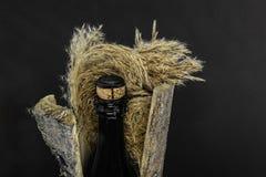 Μαύρο μπουκάλι γυαλιού CHAMPAGNE που τοποθετείται στο φλοιό δέντρων με την κλίση στο μαύρο υπόβαθρο στοκ φωτογραφία με δικαίωμα ελεύθερης χρήσης