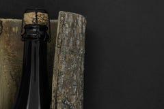 Μαύρο μπουκάλι γυαλιού CHAMPAGNE που τοποθετείται στο φλοιό δέντρων στο μαύρο υπόβαθρο στοκ εικόνες