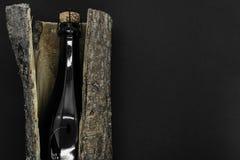Μαύρο μπουκάλι γυαλιού CHAMPAGNE που τοποθετείται στο φλοιό δέντρων στο μαύρο υπόβαθρο στοκ εικόνες με δικαίωμα ελεύθερης χρήσης