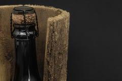 Μαύρο μπουκάλι γυαλιού CHAMPAGNE που τοποθετείται στο φλοιό δέντρων στο μαύρο υπόβαθρο στοκ εικόνα με δικαίωμα ελεύθερης χρήσης
