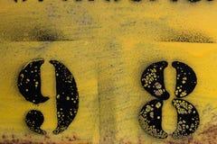 Μαύρο διάτρητο αριθμού που χρωματίζεται στο κίτρινο υπόβαθρο στοκ εικόνες