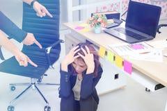 Ματαιωμένη νέα ασιατική επιχειρησιακή γυναίκα με τα δάχτυλα που δείχνει σε την στον εργασιακό χώρο του γραφείου στοκ εικόνα