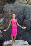 Μαυρισμένο ξανθό μαλλιαρό θηλυκό πρόσωπο που στηρίζεται στην απομονωμένη θέση της άγριας δύσκολης ακτής στοκ φωτογραφία