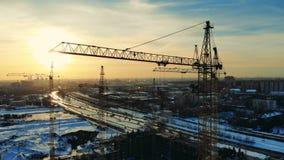 Μεγάλοι γερανοί που χτίζουν ένα σπίτι σε ένα εργοτάξιο οικοδομής σε μια πόλη απόθεμα βίντεο