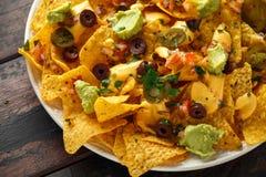 Μεξικάνικα tortilla nachos τσιπ με τις ελιές, το jalapeno, guacamole, το salsa ντοματών και την εμβύθιση τυριών κλείστε επάνω στοκ εικόνα με δικαίωμα ελεύθερης χρήσης