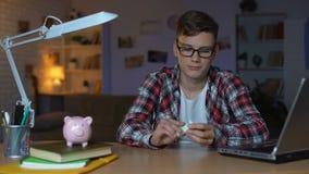 Μετρώντας λογαριασμοί δολαρίων εφήβων και τοποθέτηση τους στο σηκωήσαστε στην πλάτη, πρώτος μισθός απόθεμα βίντεο