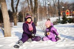 Μητέρα και αυτή λίγη κόρη που απολαμβάνει την όμορφη χειμερινή ημέρα υπαίθρια στοκ φωτογραφία