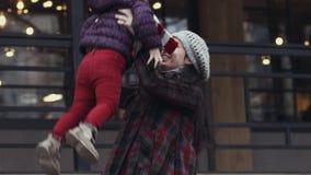 Μητέρα και κόρη που έχουν τη μεγάλη διασκέδαση μαζί στη φύση φθινοπώρου - η γυναίκα ανυψώνει επάνω το κορίτσι της οικογενειακά κα φιλμ μικρού μήκους