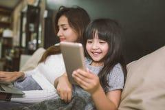 Μητέρα και κόρη που χρησιμοποιούν το smartphone και το lap-top μαζί στην κρεβατοκάμαρα απομονωμένο έννοια λευκό τεχνολογίας στοκ εικόνα με δικαίωμα ελεύθερης χρήσης