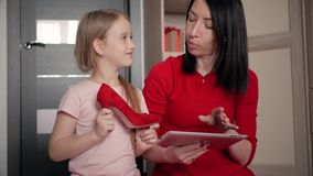 Μητέρα και λίγη κόρη που εξετάζουν τα υποδήματα ψωνίζοντας on-line στην ψηφιακή ταμπλέτα Η έννοια on-line να ψωνίσει απόθεμα βίντεο