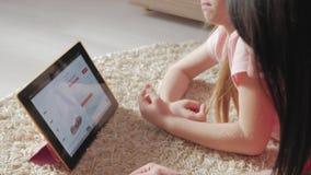 Μητέρα και λίγη κόρη που εξετάζουν τα υποδήματα ψωνίζοντας on-line στην ψηφιακή ταμπλέτα Η έννοια on-line να ψωνίσει φιλμ μικρού μήκους