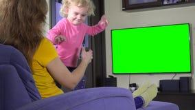 Μητέρα και το άτακτο κορίτσι κορών της που προσέχουν τη TV Πράσινη βασική οθόνη χρώματος απόθεμα βίντεο