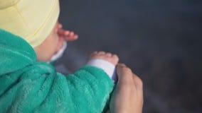 Μητέρα με το μικρό μωρό στην παραμονή χεριών της στην παραλία φιλμ μικρού μήκους