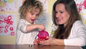 Μητέρα οικογενειακών κοριτσιών και παιδί κορών που έχει τη διασκέδαση που βάζει τα νομίσματα στη piggy τράπεζα απόθεμα βίντεο
