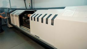 Μηχανή για την παραγωγή των άξονων εκτύπωσης Ένα άτομο θέτει - επάνω μια μηχανή Τυπωμένος άξονας με ένα αφηρημένο σχέδιο, εργοστά απόθεμα βίντεο