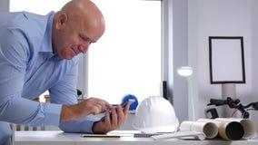Μηχανικός στο χαμόγελο γραφείων αρχιτεκτονικής που διαβάζει τις καλές ειδήσεις σε Smartphone απόθεμα βίντεο