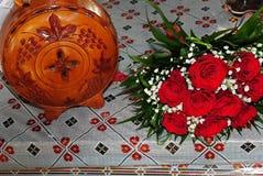 Μια ανθοδέσμη των κόκκινων τριαντάφυλλων με μια φέτα του κρασιού στοκ εικόνα