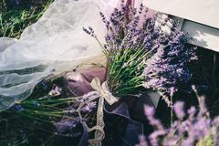 Μια ανθοδέσμη lavender που δένεται με μια δικτυωτή κορδέλλα βρίσκεται στο επιτραπέζιο πόδι στοκ εικόνες