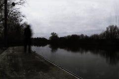 Μια απομονωμένη σκιά θόλωσε, πνευματικός με κουκούλα αριθμός κοιτάζοντας έξω σε έναν ποταμό μια χειμερινή ημέρα Με ένα κρύο, grun στοκ εικόνες με δικαίωμα ελεύθερης χρήσης