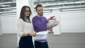 Μια γυναίκα και ένας άνδρας περπατούν κατά μήκος της αίθουσας με τα αρχιτεκτονικά σχέδια απόθεμα βίντεο