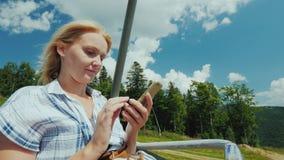 Μια γυναίκα χρησιμοποιεί ένα smartphone, οδηγά στην ανοικτή καμπίνα του τελεφερίκ Στις διακοπές σχετικά με την έννοια απόθεμα βίντεο