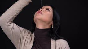 Μια γυναίκα Brunette με τα στενά μάτια σε ένα μαύρο υπόβαθρο κρατά το Andle στο χέρι της απόθεμα βίντεο