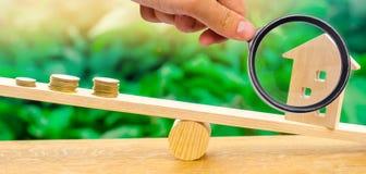 Μια ενίσχυση - το γυαλί εξερευνά έναν σωρό των νομισμάτων στις κλίμακες και ένα ξύλινο σπίτι Μηνιαία πληρωμή μισθώματος κτήμα ένν στοκ εικόνες