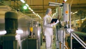 Μια εργασία προσώπων με τον εξοπλισμό εργοστασίων σε μια δυνατότητα παραγωγής προϊόντων απόθεμα βίντεο