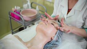 Μια επεξεργασία μασάζ προσώπου cosmetology στην κλινική Να τρίψει το μέτωπο απόθεμα βίντεο