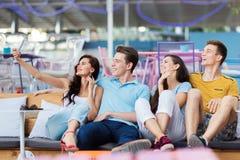 Μια επιχείρηση των όμορφων φίλων γελά και κάθεται στον πάγκο με τα μαξιλάρια και κάνει selfie στο συμπαθητικό στοκ φωτογραφίες