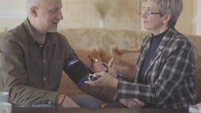 Μια ηλικιωμένη γυναίκα μετρά την πίεση στον ώριμο σύζυγό της Το ώριμο ζεύγος ξοδεύει το χρόνο από κοινού Προσοχές συζύγων για φιλμ μικρού μήκους
