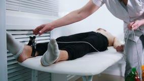 Μια ιατρική κλινική Ένα άτομο που λαμβάνει μια διαδικασία ECG Αφαίρεση του ιατρικού εξοπλισμού από τα άκρα πελατών απόθεμα βίντεο